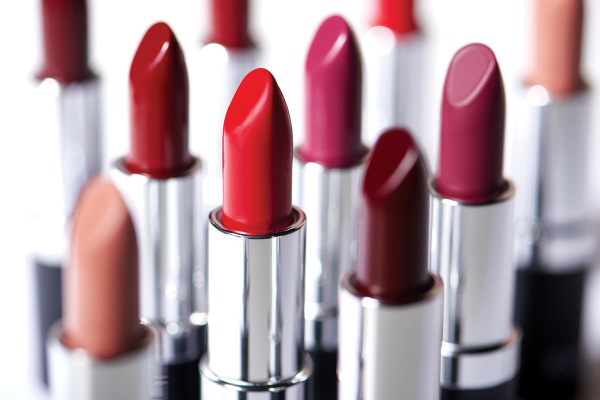 An up-close display of ZOYA lipsticks, including nude, red, and pink colors.