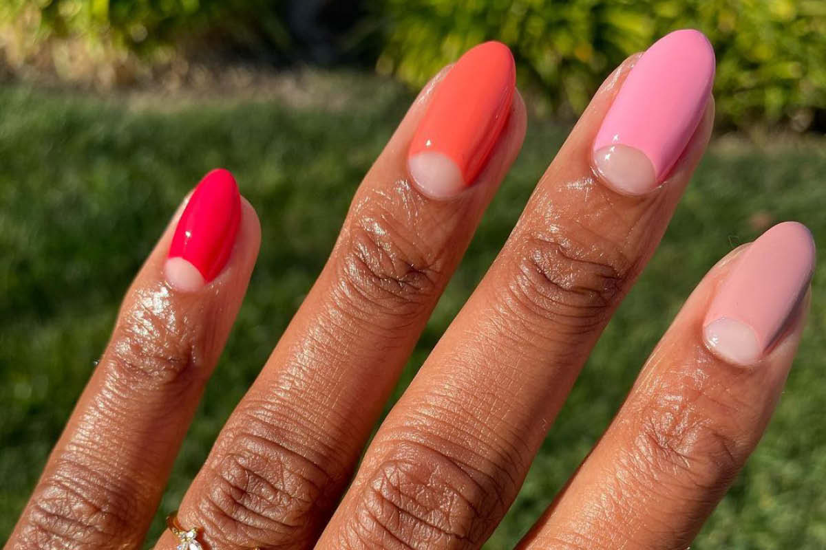 A hand in front of an outdoor landscape background is showing a skittle manicure of the ZOYA Darling Collection, with half-moon negative space on each nail.