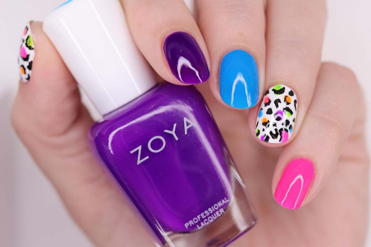 A hand holding a bottle of ZOYA in Banks, displaying shades from the EasyNeon collection in a skittle manicure with neon leopard print accent nails on the thumb and ring fingers.