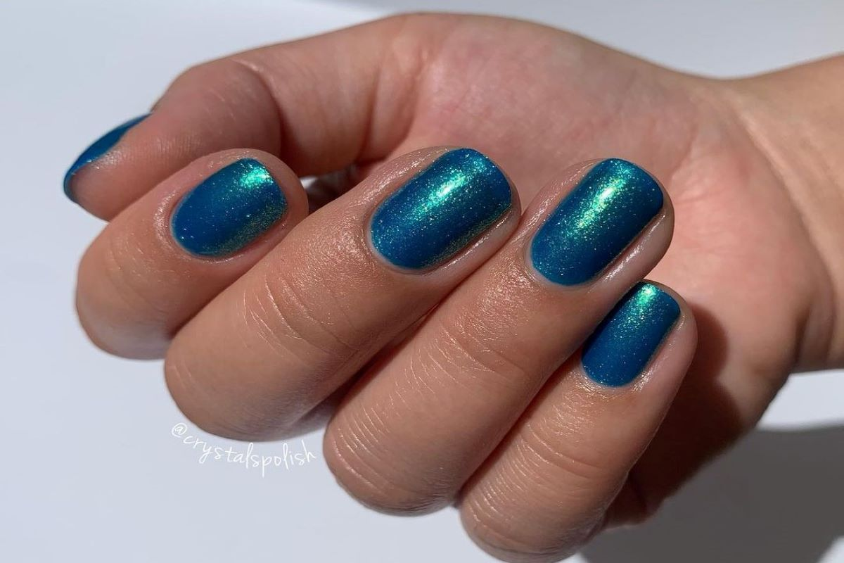 A hand is showing the color Summer by Zoya on her fingernails.