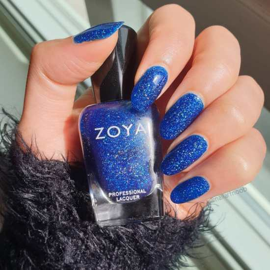 A hand showing Dream by Zoya painted on the fingernails while holding the Zoya bottle.