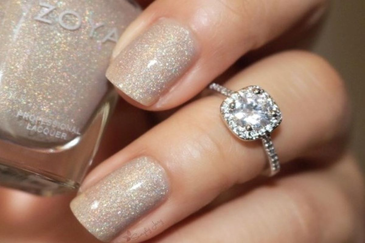 A hand is shown wearing ZOYA Brighton on the fingernails while holding the polish bottle. A diamond ring is worn on the ring finger.