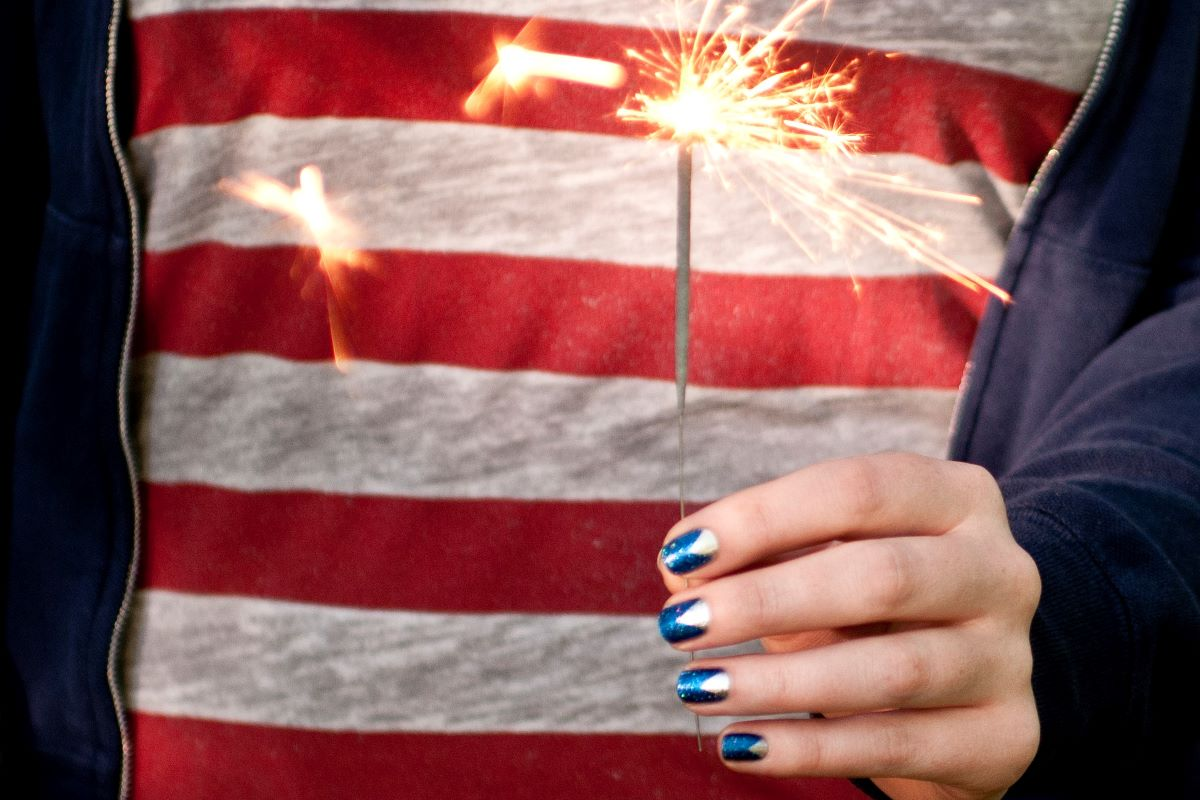 A hand with July 4 nail art is holding a sparkler in front of her American flag shirt.
