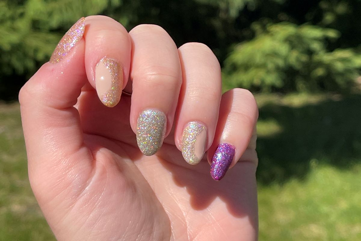 A hand showing the Zoya colors April, Celestia, Polaris and Eradani on the nails with two accent nails in a half-moon design.