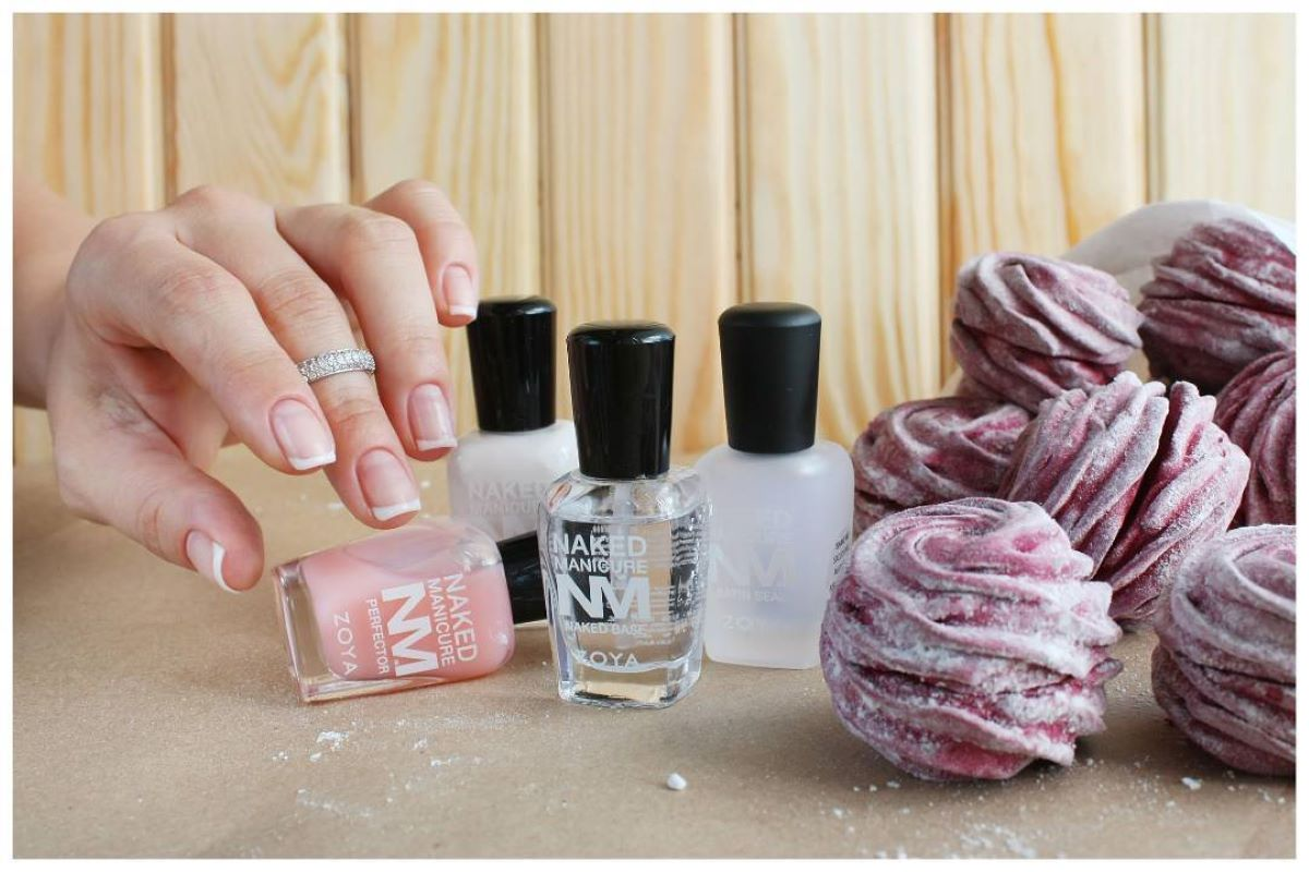 A hand is positioning a Naked Manicure Perfector next to other Naked Manicure products.