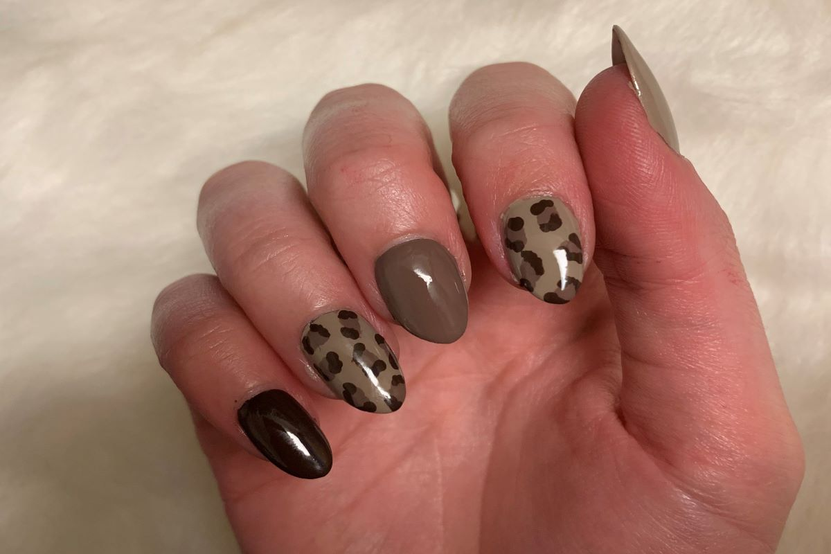 A neutral manicure with leopard print nail art on two accent nails.