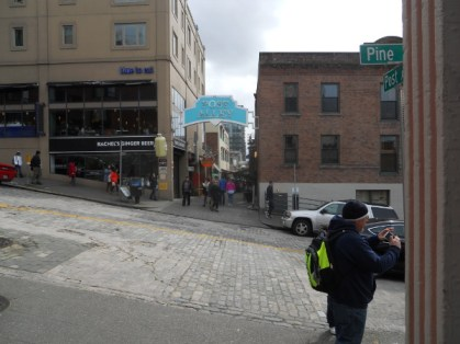 "The guy on the right is photographing the ""Public Market"" sign"