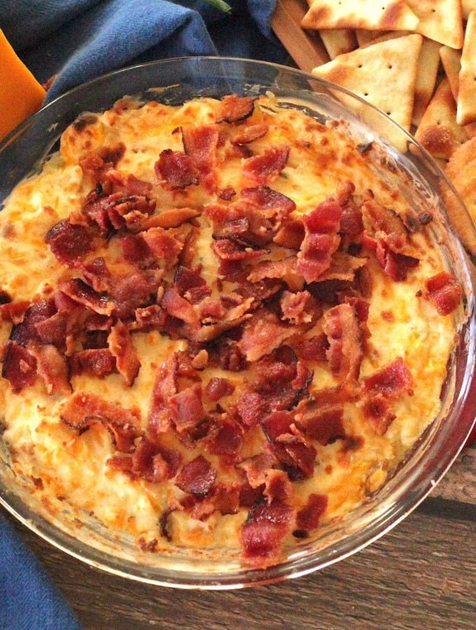 Image of a glass pie pan with hot cheddar cheese dip topped with crispy bacon.