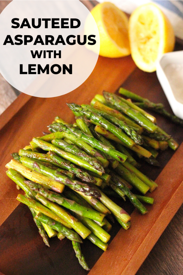 Sauteed asparagus with lemon on a wooden serving plate