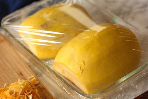 spaghetti squash in a baking dish covered with plastic wrap