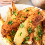 air fried potato wedges on a plate with greek yogurt dipping sauce