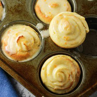 orange rolls in a muffin tin