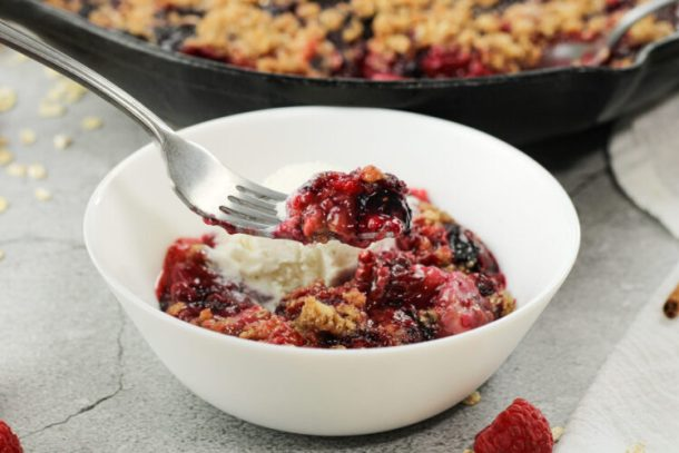 fork holding some triple berry crisp