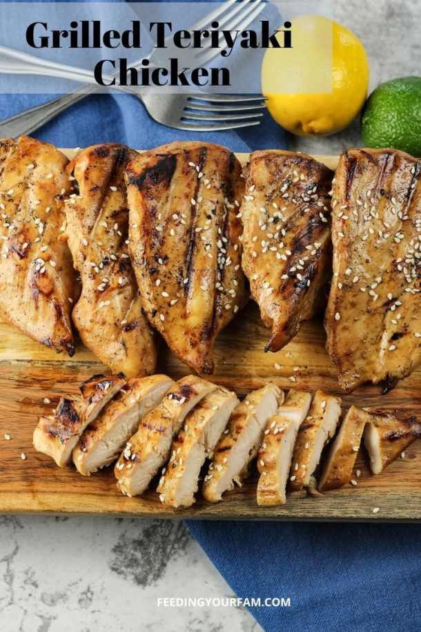 grilled chicken on a wooden cutting board. One chicken breast is sliced