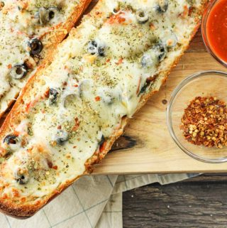 stuffed french bread pizza halves on a wooden platter