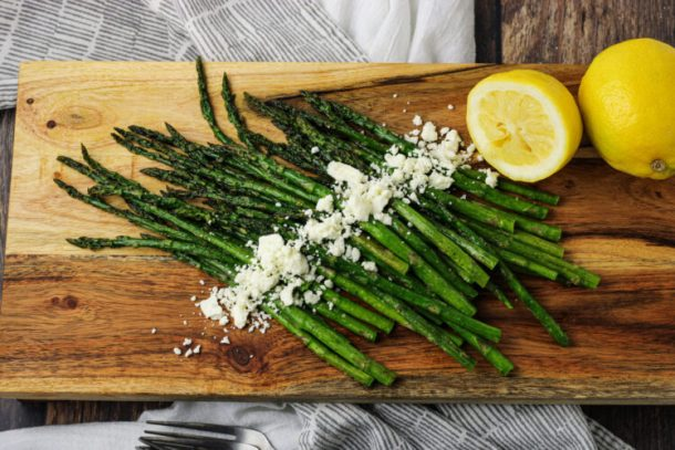 asparagus on wooden platter with lemons and feta