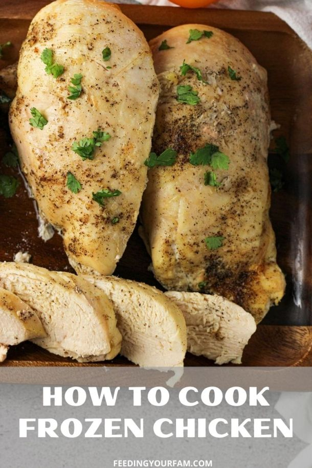 cooked chicken breasts on a wooden platter with chopped parsley sprinkled on top