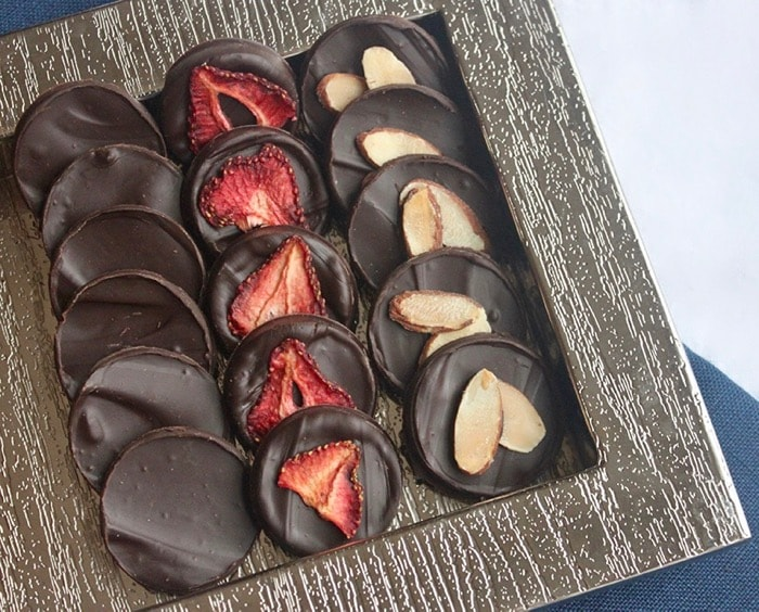 homemade dark chocolate coins with dried strawberries and toasted almonds are a delicious paleo holiday dessert