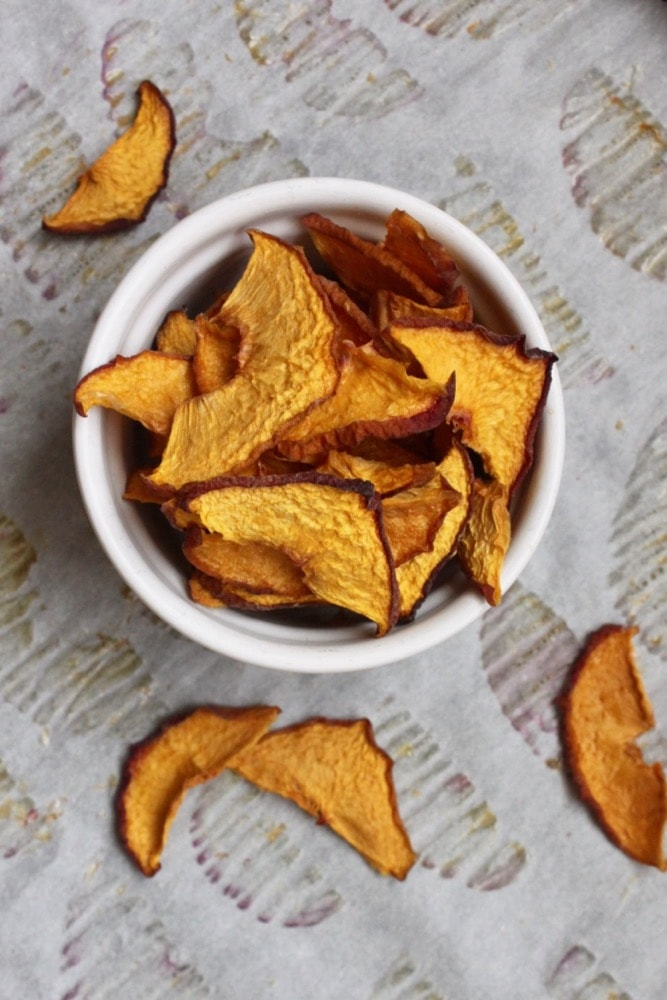 oven dried peach chips in a white bowl with chips scattered on parchment paper