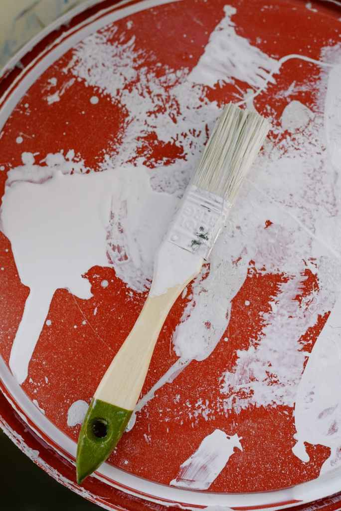brush in white paint placed on bottle lid
