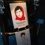 Hand drawn image of Malala Yousafazi wearing a red hijab, image is displayed on a small easel and has light shining on it.