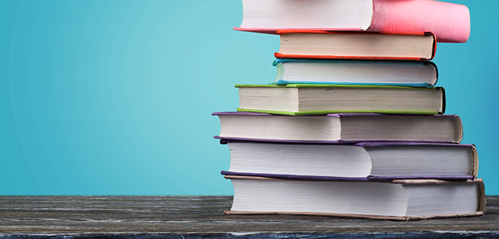 stack of colorfully bound books against turquoise background on dark wood table