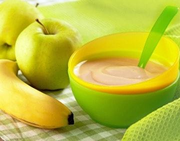 A bowl of baby food sitting on a table with an apple and a banana