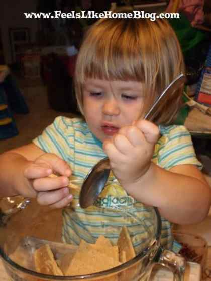A little girl stirring food in a bowl