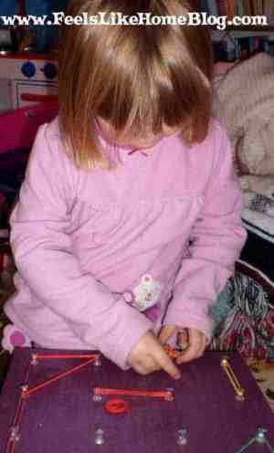 A little girl using her geoboard