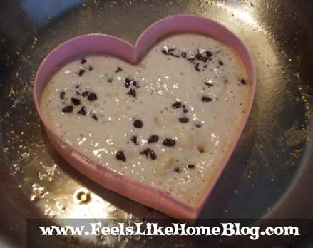A pancake cooking with chocolate chips and heart
