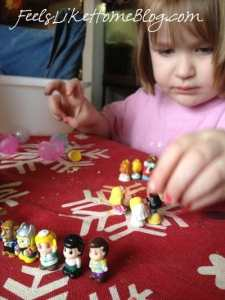 A little girl sitting at a table playing with tiny toys