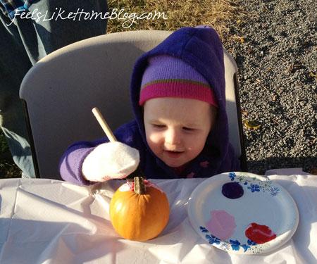 A little sister painting a pumpkin