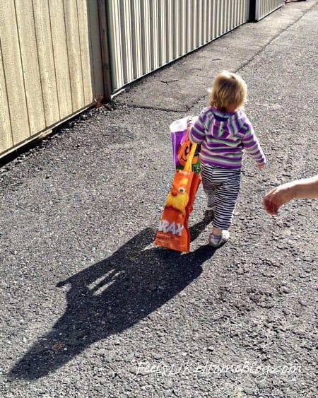 A little girl walking on a sidewalk