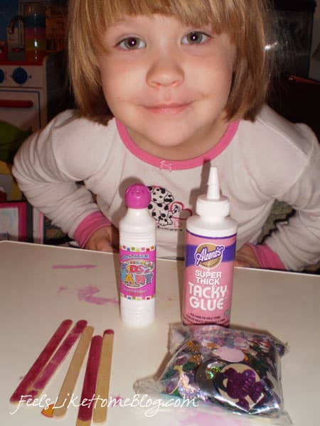 A little girl sitting at a table with craft supplies
