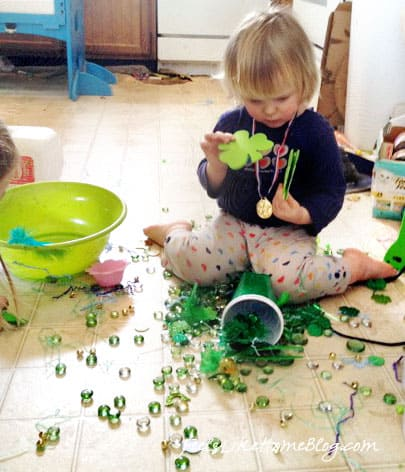 A small child sitting on the floor with a big mess