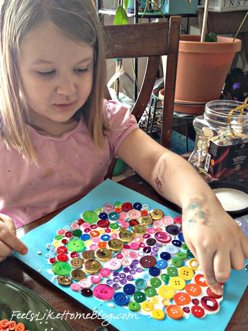 A little girl gluing buttons onto a piece of paper
