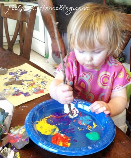 A little girl using a stick as a paint brush