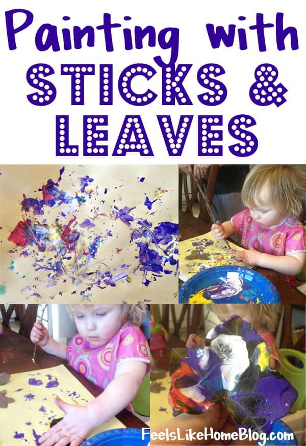 A little girl painting with sticks and leaves