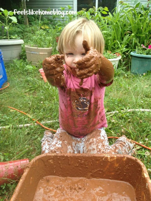 A little girl dropping mud into a bucket