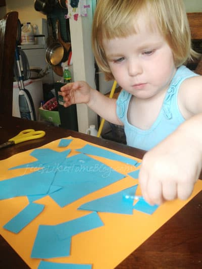 A little girl gluing a blue collage onto orange paper