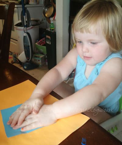 A small child gluing blue paper to orange paper