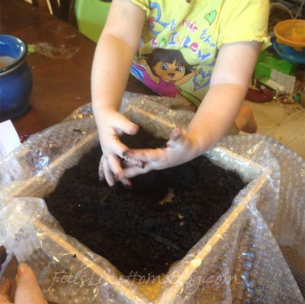 A little girl putting soil into her fairy garden