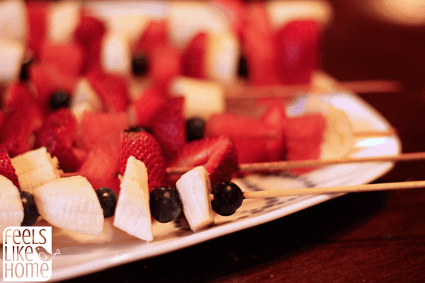 A close up of red white and blue fruit kabobs