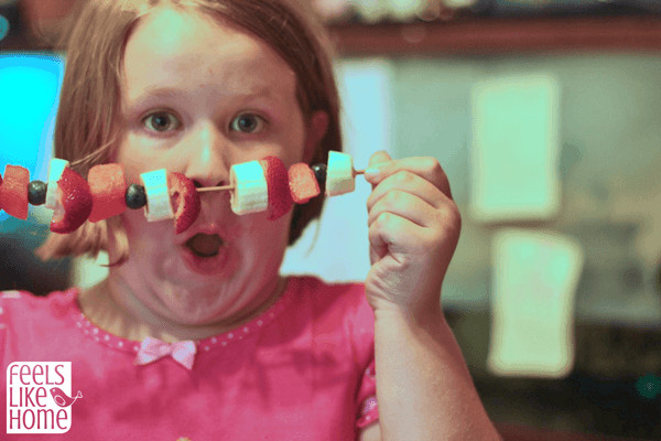 A little girl holding her fruit kabob up like a mustache