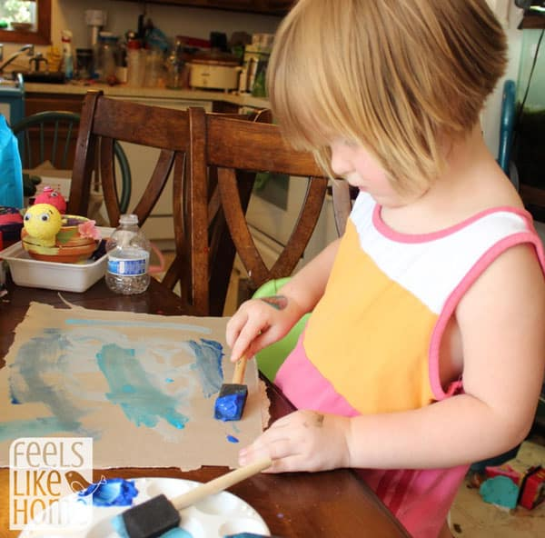A little girl painting cardboard