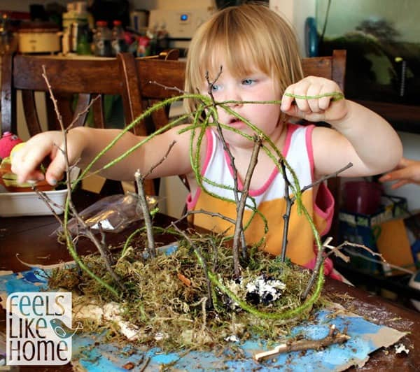 A small child adding vines to her island