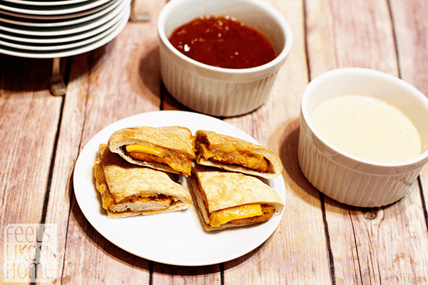 A cup of ketchup sitting on top of a wooden table, with Sandwich and Flatbread