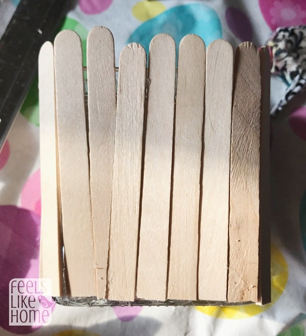 Gluing popsicle sticks to the candle holder