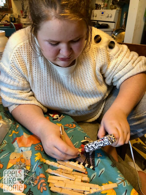 A girl gluing clothespins together
