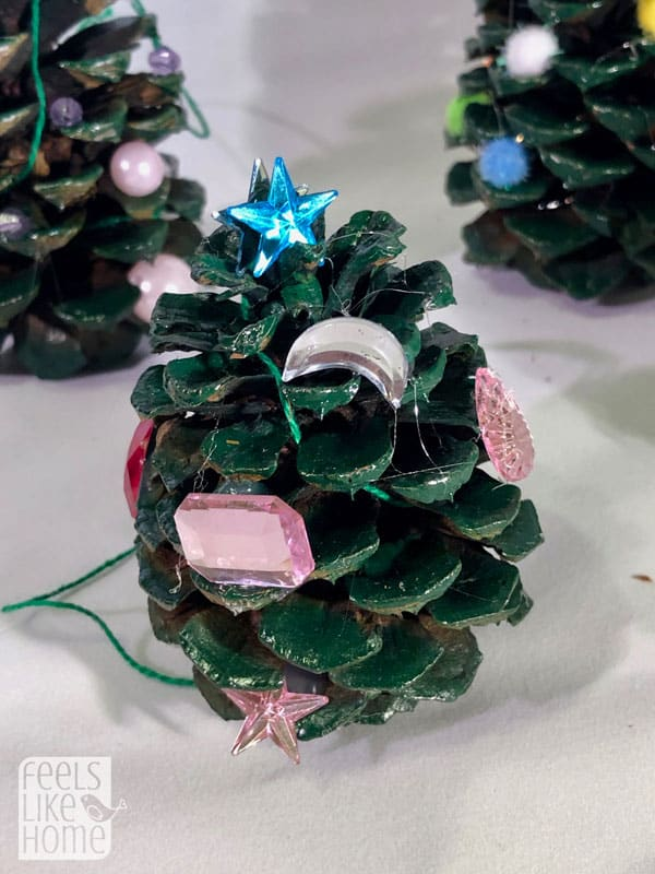 A close up of a pine cone Christmas tree with jewels for ornaments